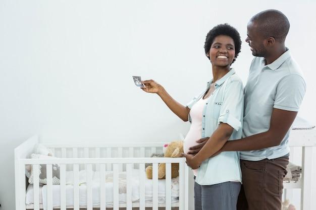 Pareja embarazada con ecografía cerca de la cuna del bebé en casa