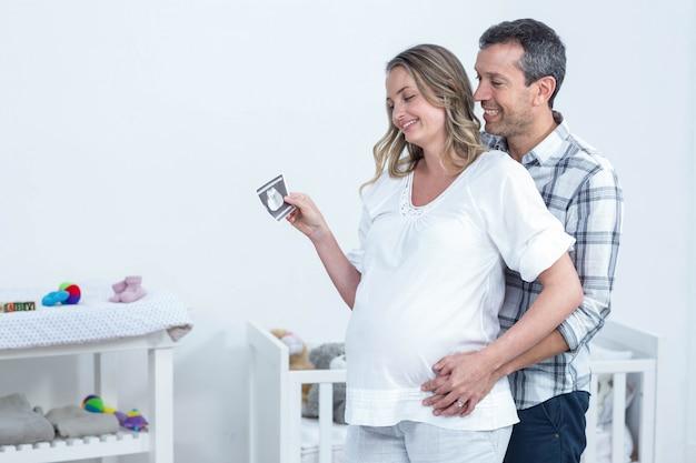 Pareja embarazada con informe de ecografía en casa