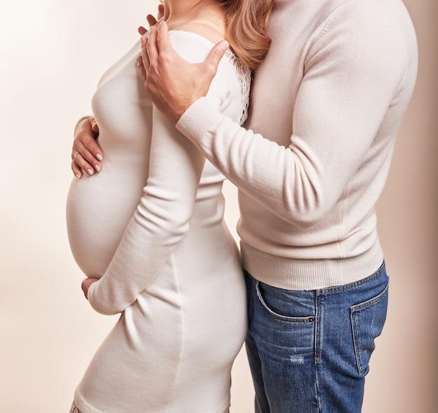 Pareja embarazada en un marco sin rostro
