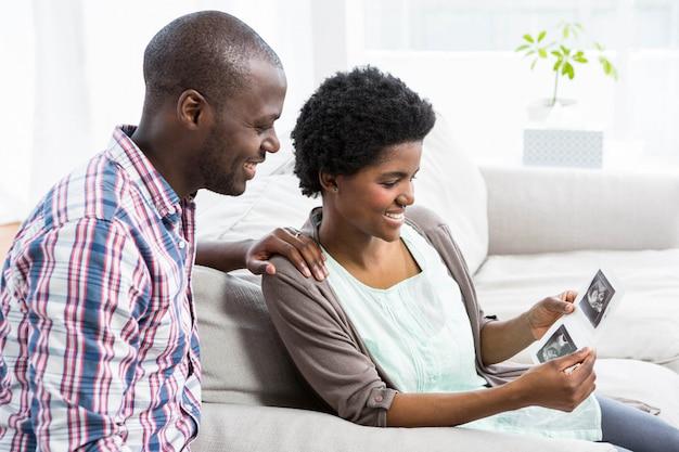 Pareja embarazada sentada en el sofá y mirando la ecografía en casa
