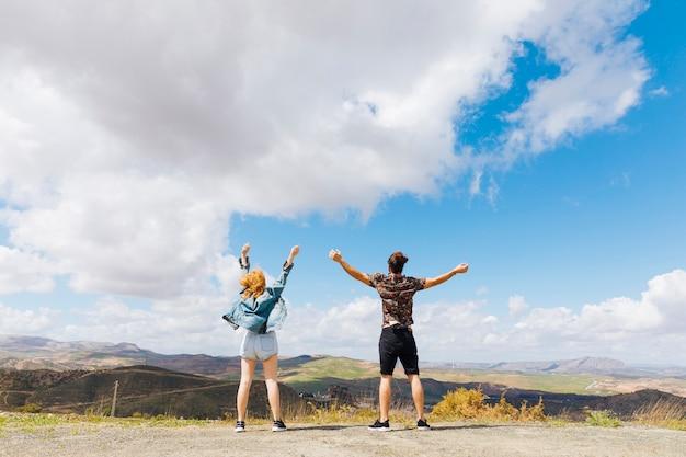 Pareja emocionada con las manos arriba en la cima de la colina