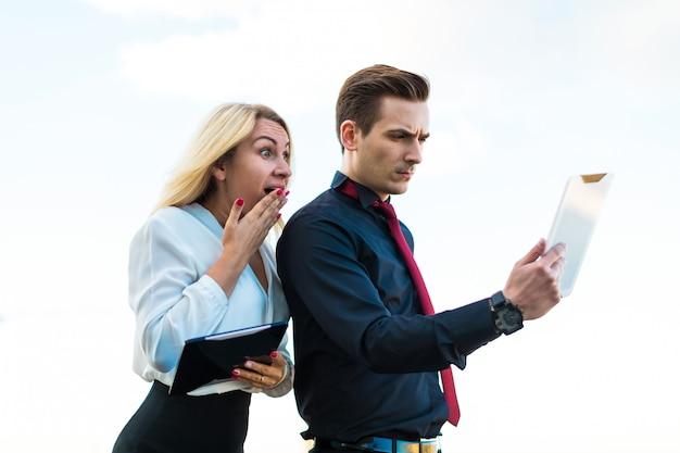 Pareja de empresarios, guapo hombre morena y atractiva mujer rubia de pie en el techo y mirar en tabletas