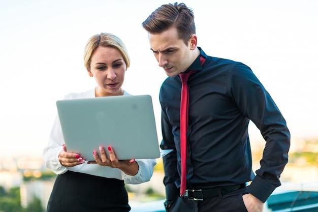 Pareja de empresarios, hombre moreno serio y atractiva mujer rubia de pie en el techo y mirar en la computadora portátil