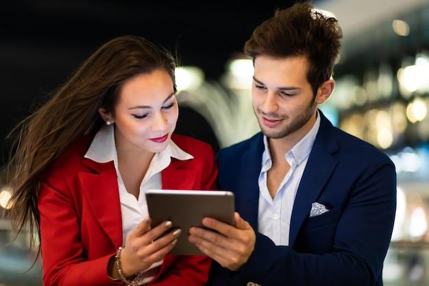 Pareja de empresarios que usan una tableta al aire libre por la noche en un entorno de ciudad moderna