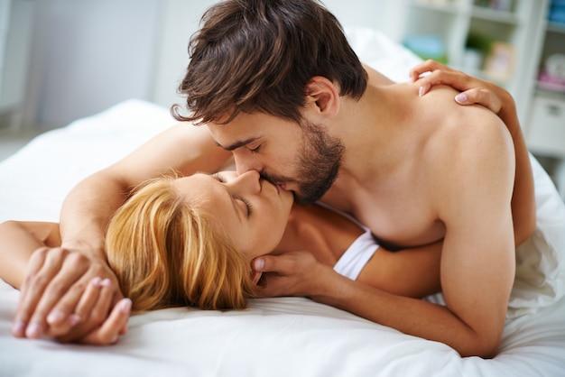 Pareja enamorada besandose en la cama