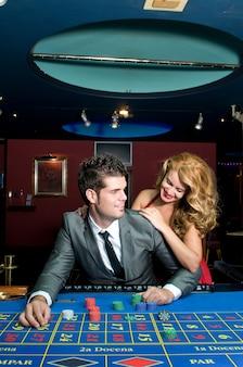 Pareja enamorada ganando dinero en las mesas del casino