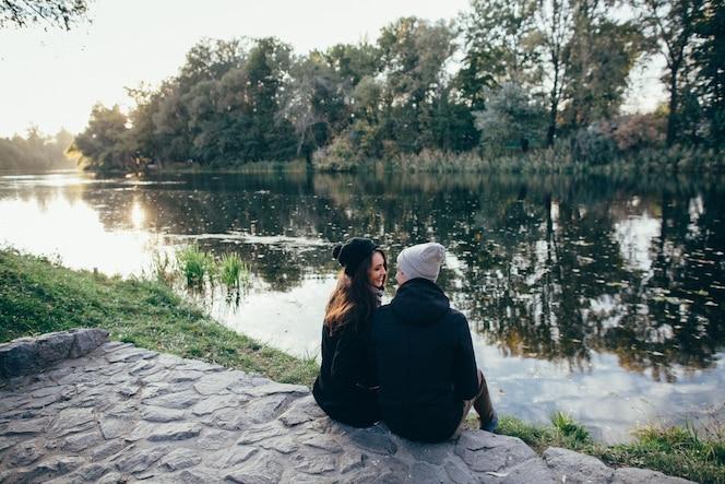 Pareja enamorada. hermosa pareja de enamorados en ropa de abrigo se sienta en riverside al atardecer.