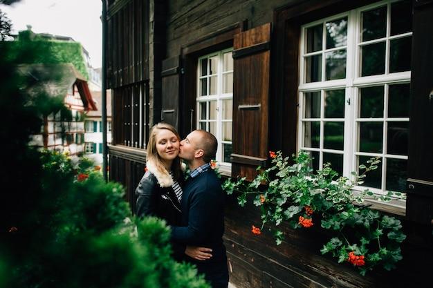 Pareja enamorada. hombre besando a su propia novia en la mejilla. hermosa pareja besándose al aire libre