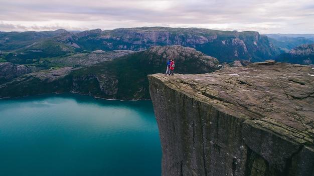 Pareja enamorada preikestolen masivo acantilado (noruega, lysefjorden vista de la mañana de verano)
