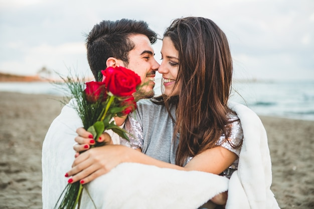 Pareja enamorada sentada en una playa con un ramo de rosas