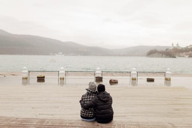 Pareja enamorada sentada sola en el muelle