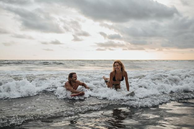 Pareja enamorada va a surfear juntos