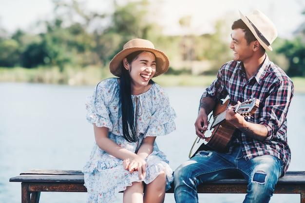 Pareja enamorada de tocar la guitarra en el río