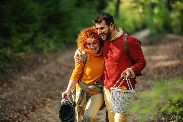 Pareja de enamorados abrazándose y caminando en la naturaleza. la pareja tiene equipo de picnic. otoño.