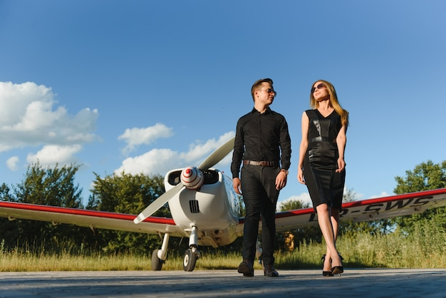 Pareja de enamorados abrazándose cerca de avión privado