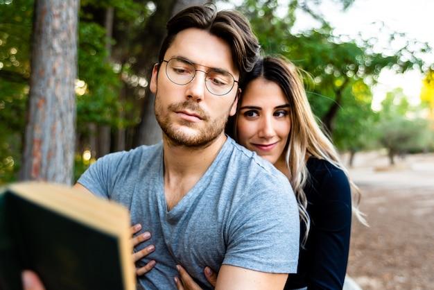 Pareja de enamorados abrazándose, leer un libro en un jardín natural.