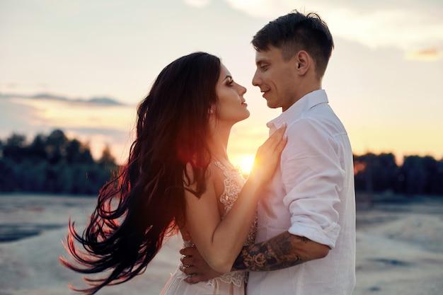 Pareja de enamorados abrazos beso feliz vida puesta de sol rayos