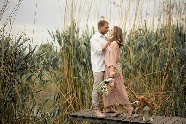 Pareja de enamorados abrazos y besos en el muelle de madera en la naturaleza.