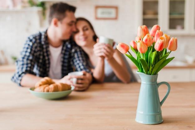 Pareja de enamorados acurrucados en la mesa y disfrutando del té