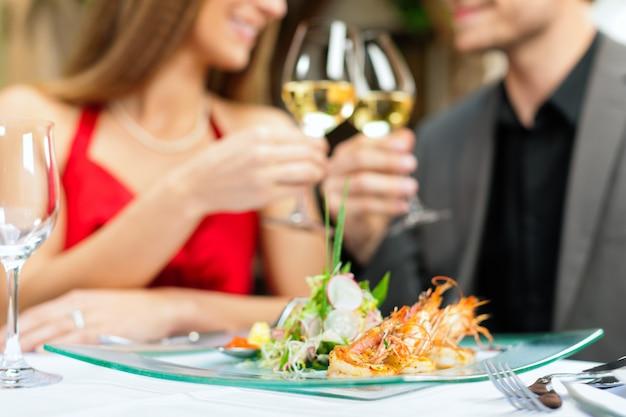 Pareja de enamorados brindando con champán en el restaurante