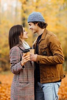 Pareja de enamorados con bufandas se sienta en el parque sosteniendo tazas de té o café