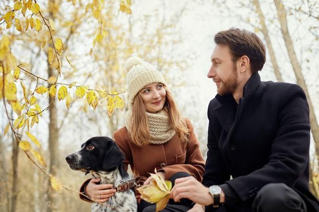 Pareja de enamorados en un cálido día de otoño camina en el parque con alegre perro spaniel