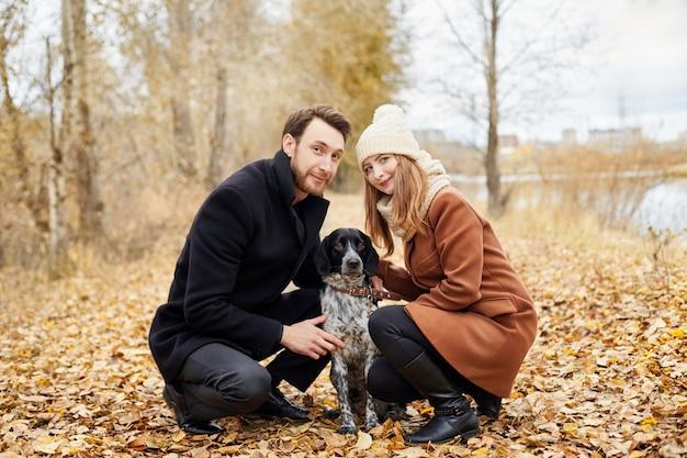 Pareja de enamorados en un cálido día de otoño camina en el parque con un alegre perro spaniel