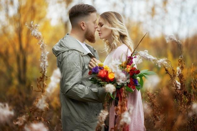 Pareja de enamorados camina por el bosque de otoño. abrazos y besos de hombres y mujeres, relaciones y amor. joven pareja se encuentra en la hierba roja amarilla, un ramo de flores en la mano de niña