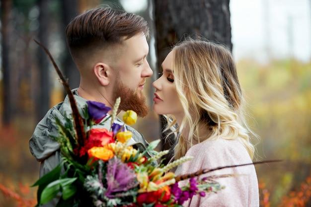 Pareja de enamorados camina por el bosque de otoño. abrazos y besos de hombres y mujeres, relaciones y amor. pareja joven se encuentra en amarillo rojo hierba, un ramo de flores en mano de mujer