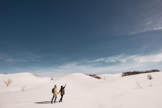 Pareja de enamorados camina en invierno en la nieve. hombre y mujer viajando. pareja de enamorados en las montañas. viajeros en las montañas. paseo de invierno aventuras de invierno pareja amorosa