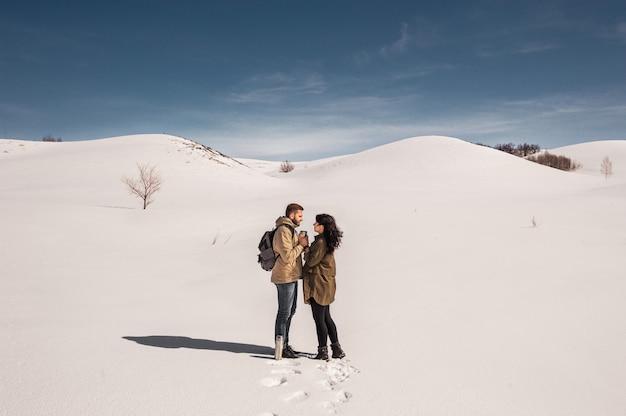 Pareja de enamorados camina en invierno en la nieve. hombre y mujer viajando. pareja de enamorados en las montañas.