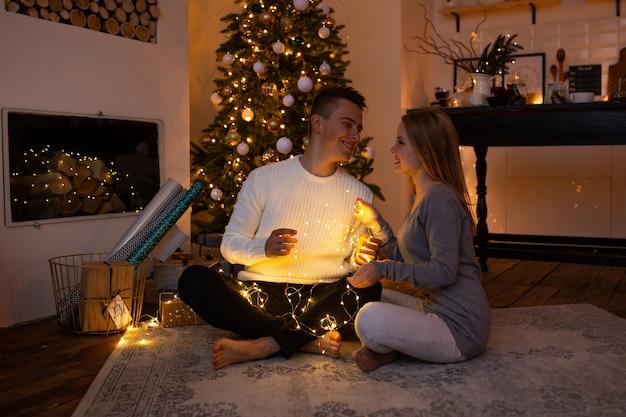 Pareja de enamorados en casa en el árbol de navidad en el fondo luz mágica