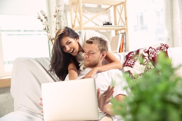 Pareja de enamorados en casa relajándose juntos. hombre y mujer caucásicos que tienen fin de semana, se ve tierna y feliz