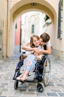 Pareja de enamorados en el casco antiguo de la ciudad. niña con enfermedad en una silla de ruedas y su hombre encantador, abrazándola por la espalda