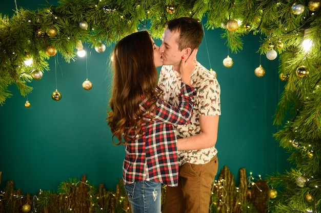 Pareja de enamorados cerca de las decoraciones de navidad joven pareja besándose cerca del árbol de navidad. clave baja. silueta.