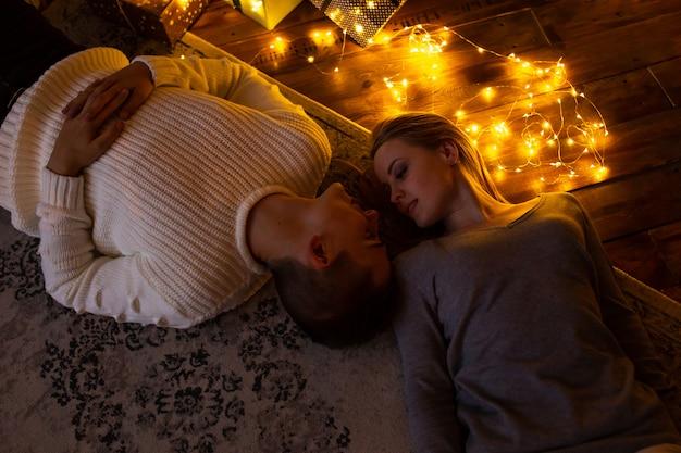 Pareja de enamorados cerca de guirnalda de navidad tirado en el piso en casa