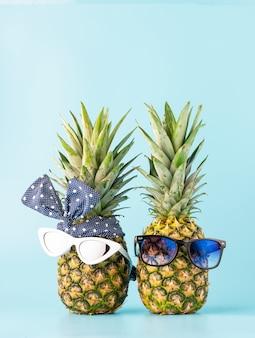 Pareja de enamorados de compras en un resort de vacaciones. piñas con gafas en forma de un chico y una chica sobre un fondo claro