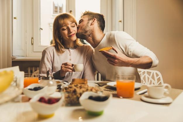 Pareja de enamorados desayunando temprano en la mañana en la cocina de casa y pasando un buen rato.