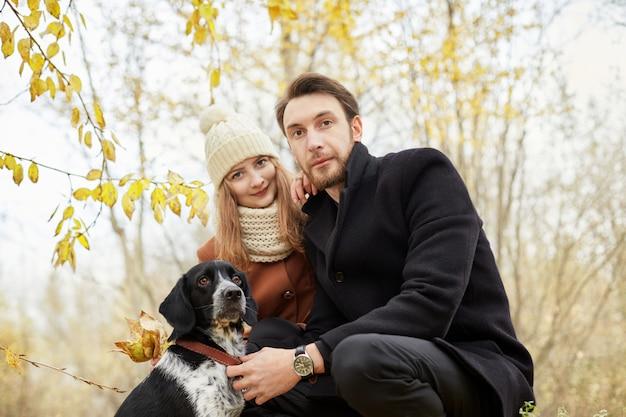 Pareja de enamorados en el día de san valentín caminando en el parque con el perro.