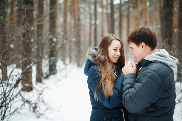 Pareja de enamorados divirtiéndose en las vacaciones de invierno. bosque de invierno de nieve en el fondo.