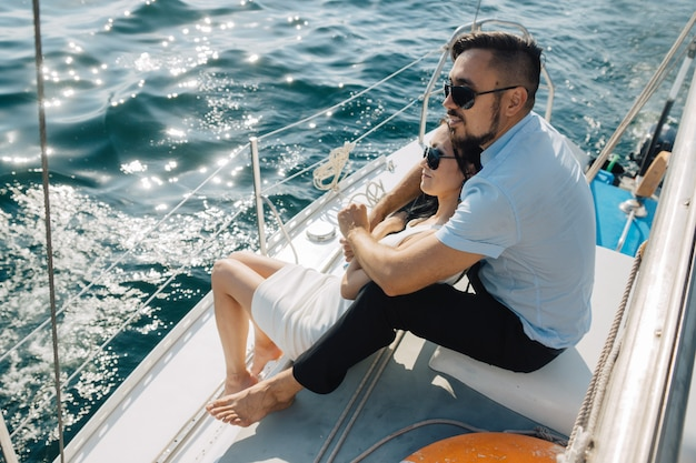 Pareja de enamorados están sentados en la cubierta del yate, abrazados. la pareja mira al horizonte.