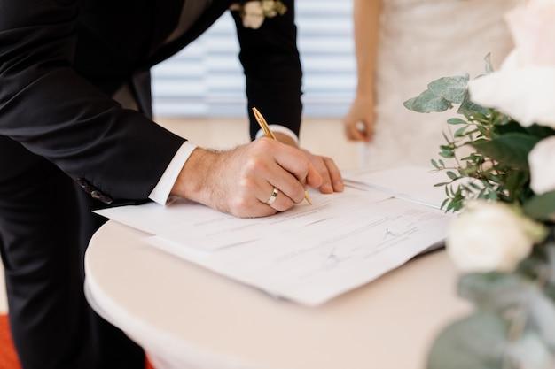 Pareja de enamorados firma documentos oficiales de matrimonio
