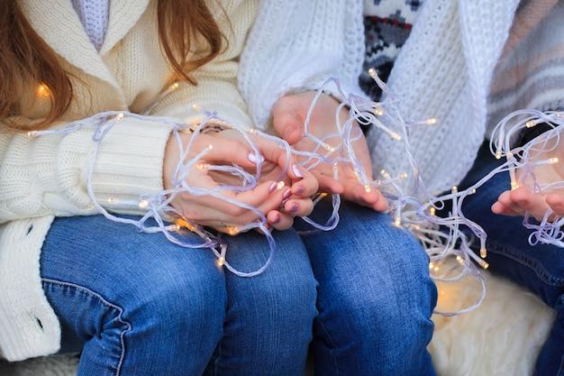 Pareja de enamorados con una guirnalda de navidad. primer plano de las manos