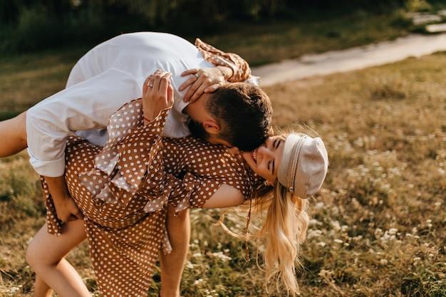 Pareja de enamorados jugando en el parque. marido y mujer abrazándose, besándose y divirtiéndose.