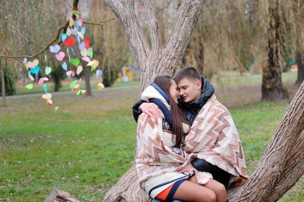Pareja de enamorados bajo una manta se calienta en el parque de otoño.