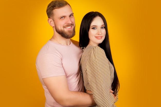 Una pareja de enamorados en una pared amarilla, hermosos recién casados, un hombre abrazando a una mujer, con copia espacio. el concepto de una relación feliz, familia joven.