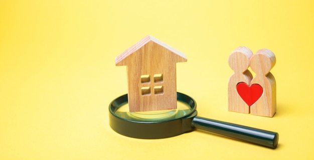 Una pareja de enamorados está de pie junto a la casa y una lupa.