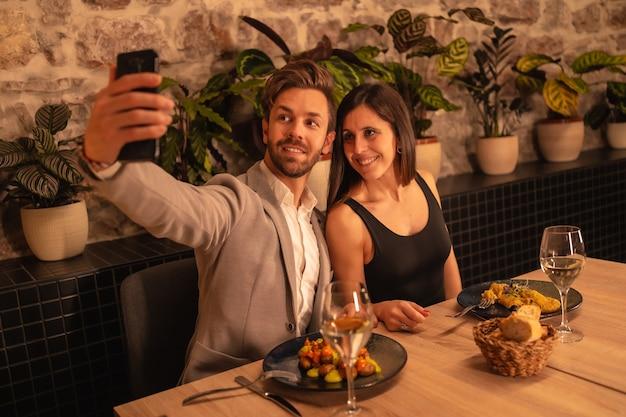 Pareja de enamorados en un restaurante, divertirse cenando juntos, celebrando el día de san valentín, tomando un selfie de recuerdo