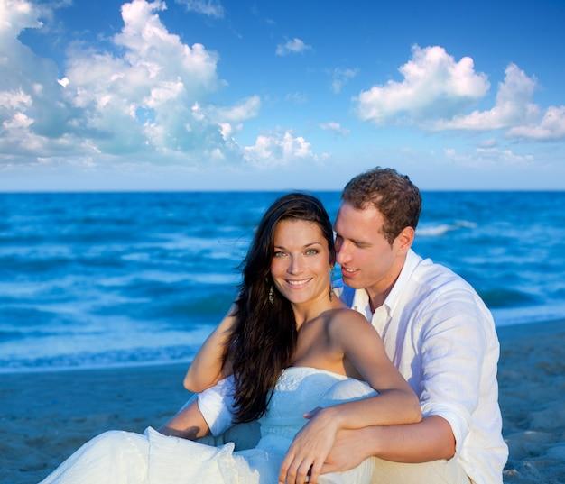 Pareja de enamorados sentados en la playa azul