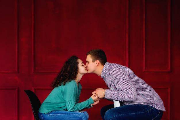 Una pareja de enamorados sentados en las sillas y besándose contra una pared decorada en rojo